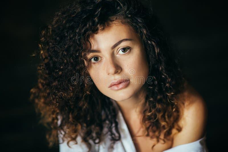 一美丽的少女的画象在一个黑暗的演播室 卷发 图库摄影