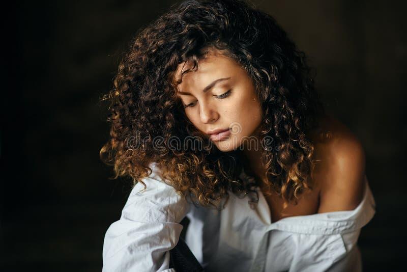 一美丽的少女的画象在一个黑暗的演播室 卷发 免版税图库摄影