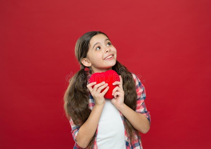 一爱一心脏 拿着红色心脏的小女孩 有心脏问题和心伤 表现出的小孩爱  库存照片