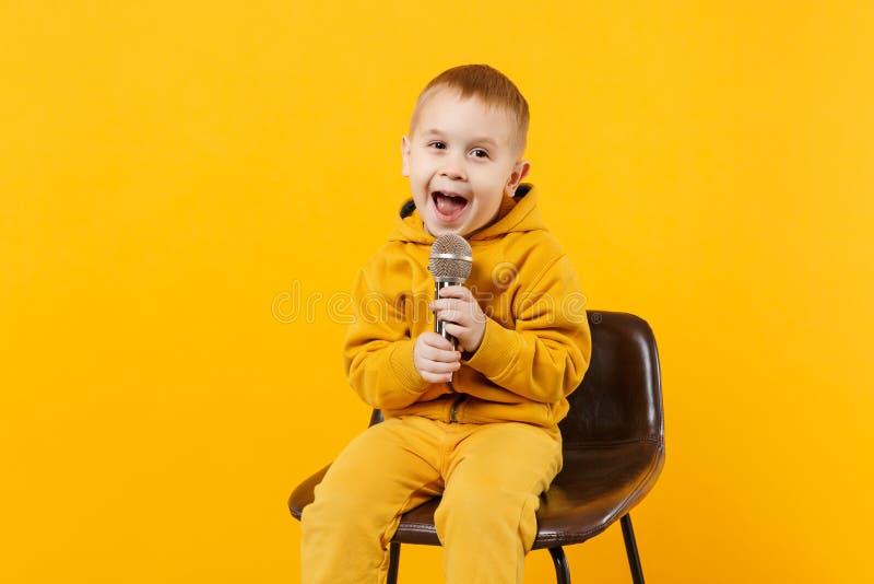 一点乐趣孩子男孩在黄色衣裳的3-4岁唱在明亮的橙色墙壁背景隔绝的话筒的歌曲 库存照片