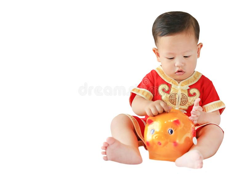 一点亚裔男婴用把有些硬币放的传统中国礼服入被隔绝的存钱罐在白色背景上 孩子挽救 免版税库存照片