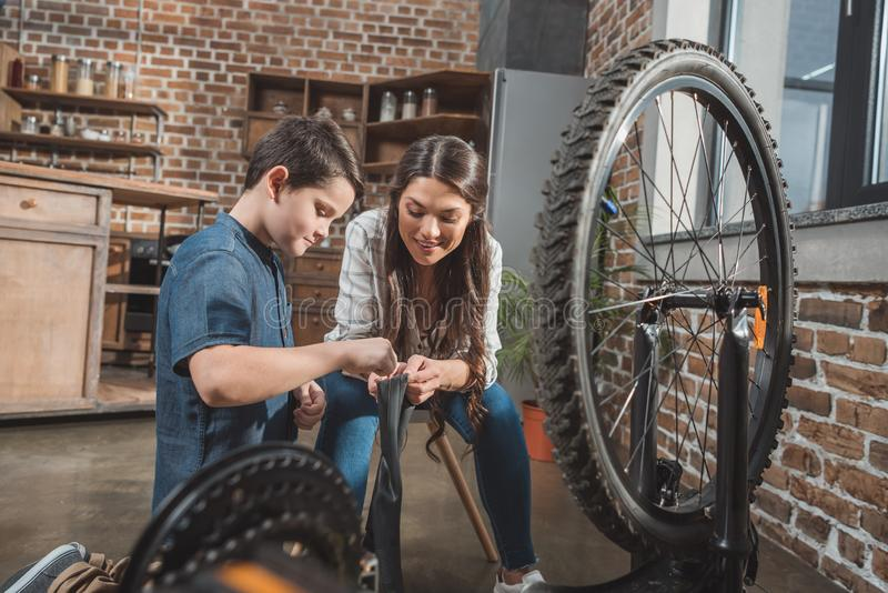 一点修理一个放气的自行车轮胎的儿子和他美丽的母亲 免版税库存照片