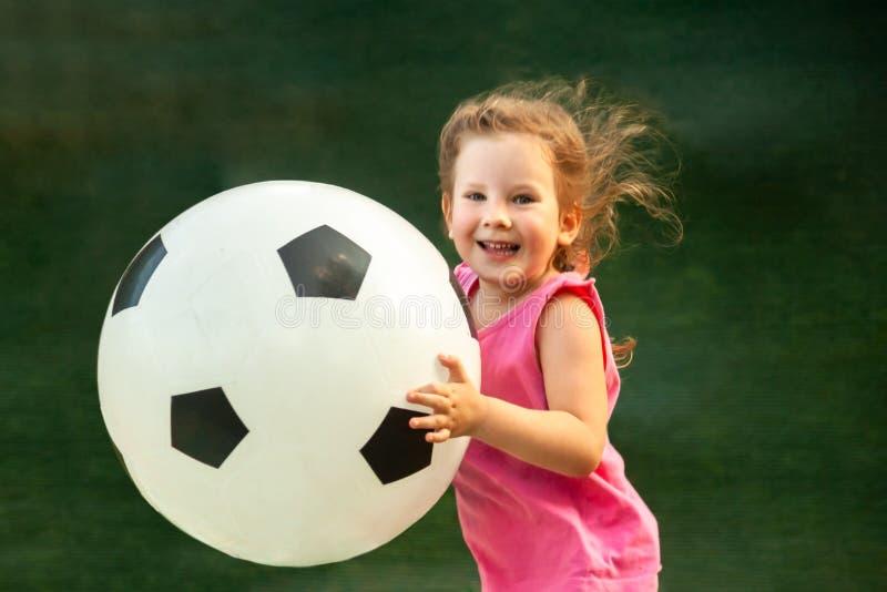 一点女婴跑与一个巨大的足球 免版税库存图片