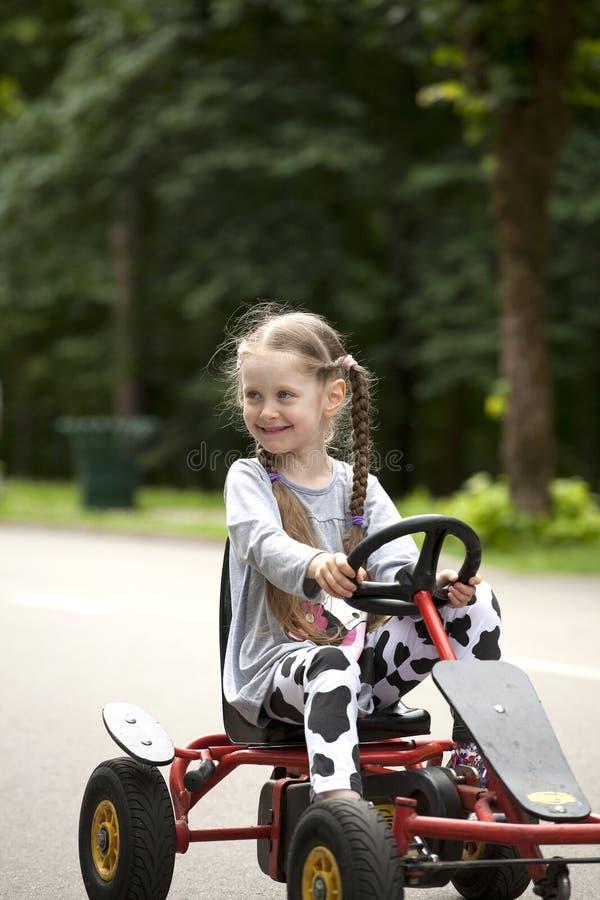 一点微笑的女孩在赛车amusemant公园 免版税库存照片