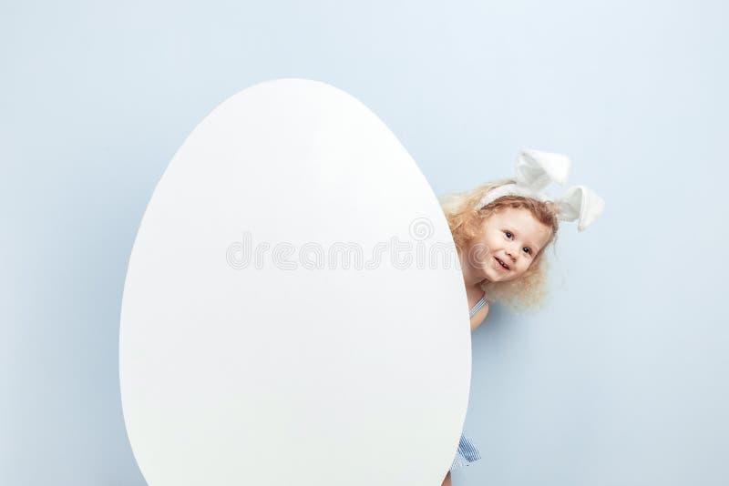 一点有兔宝宝耳朵的卷曲女孩在她的掩藏在一个大白鸡蛋后的头对蓝色墙壁 兔宝宝复活节 免版税图库摄影