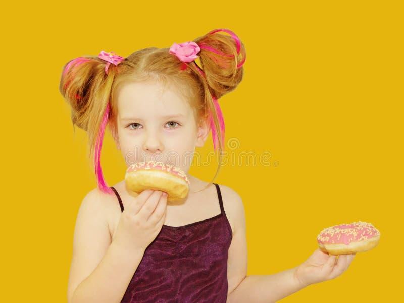 一点愉快的逗人喜爱的女孩吃着在橙色背景墙壁上的多福饼 库存照片