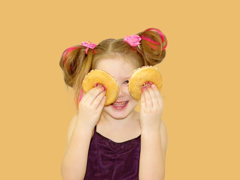 一点愉快的逗人喜爱的女孩吃着在橙色背景墙壁上的多福饼 图库摄影