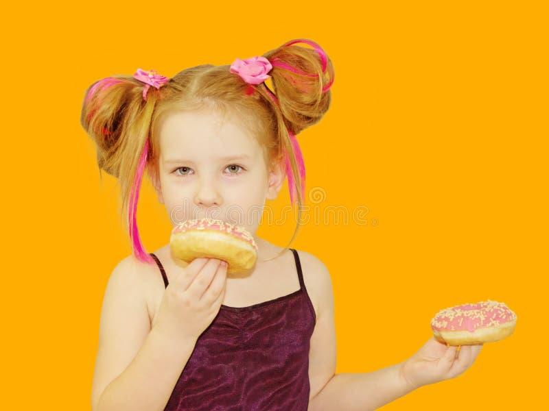 一点愉快的逗人喜爱的女孩吃着在橙色背景墙壁上的多福饼 库存图片