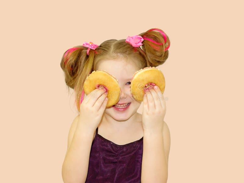 一点愉快的逗人喜爱的女孩吃着在橙色背景墙壁上的多福饼 免版税库存图片