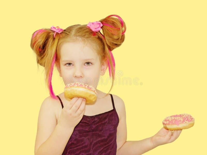 一点愉快的逗人喜爱的女孩吃着在黄色背景墙壁上的多福饼 图库摄影