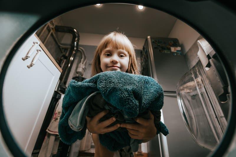 一点迷人的女孩在洗衣机投入衣裳在卫生间里 免版税库存照片