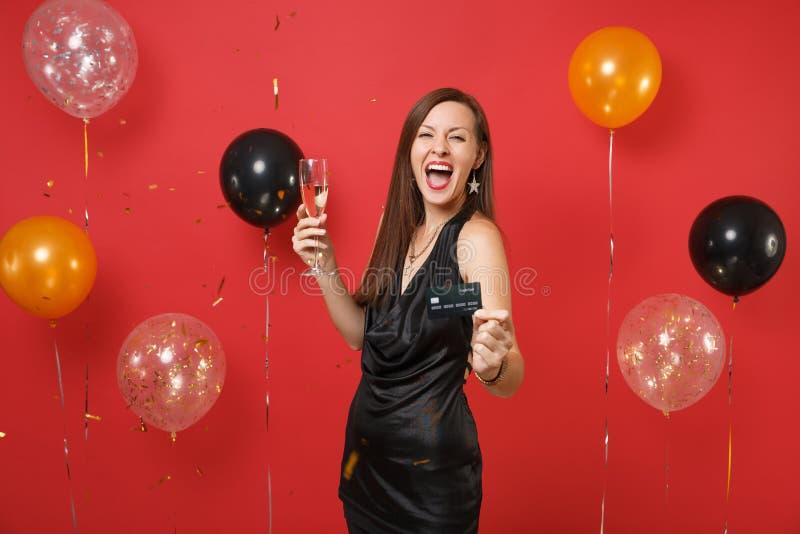 一点黑礼服尖叫的庆祝的极度高兴的年轻女人,拿着信用卡杯在明亮的红色的香槟 免版税图库摄影