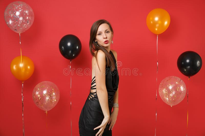 一点黑礼服的热情的年轻女人庆祝在明亮的红色背景气球的吹的嘴唇 华伦泰` s 库存图片