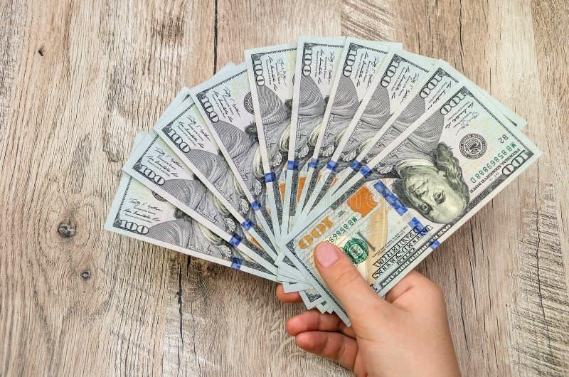 一百元钞票在一名妇女的手上木背景的 免版税库存图片