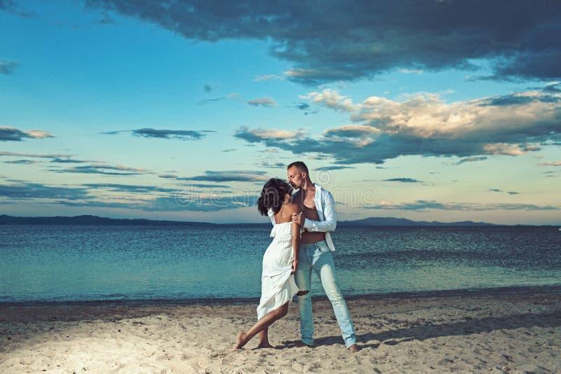 一起享受夏日的亲吻的夫妇的爱联系 家庭和情人节 在爱的夫妇放松在海滩 免版税库存照片