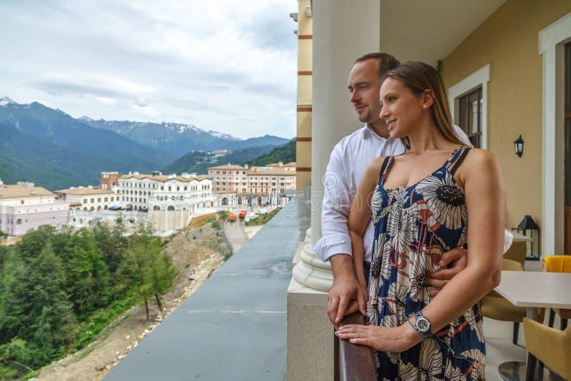 一起享受在前索利斯餐馆的大阳台的年轻愉快的白种人夫妇一个风景夏天山景身分  库存照片