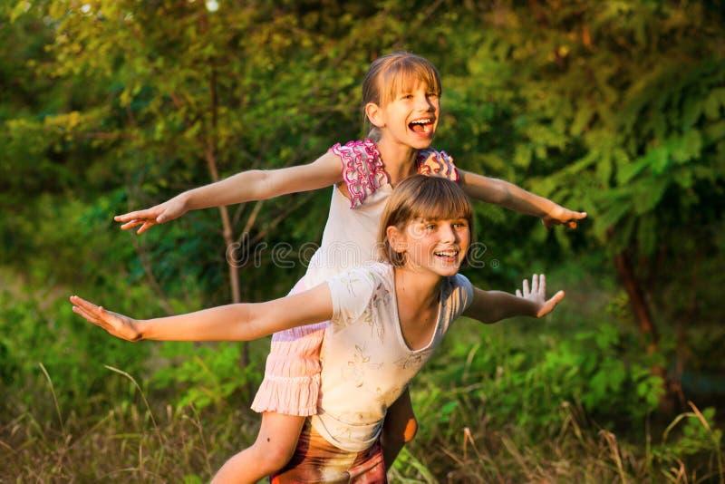 一起使用两个儿童的女孩 姐妹演奏超级英雄 有愉快的孩子乐趣,微笑和拥抱 免版税库存照片