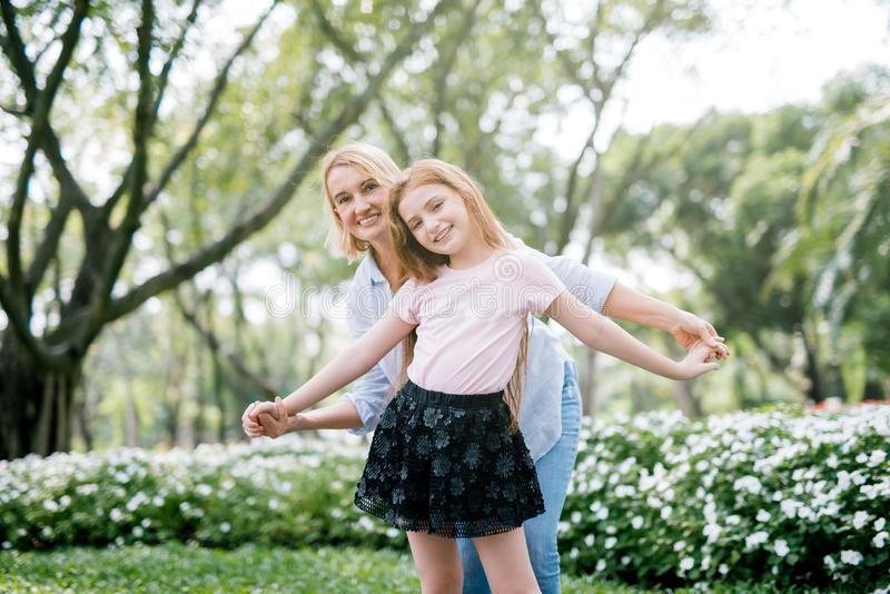 一起使用在公园的年轻愉快的美丽的母亲和女儿画象  库存图片