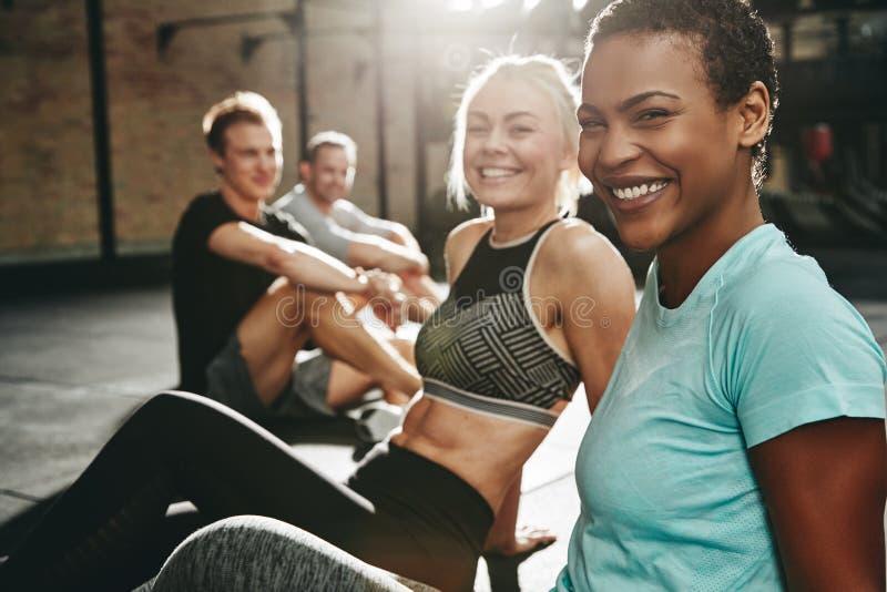 一起坐在健身房的两笑的年轻女人 库存照片