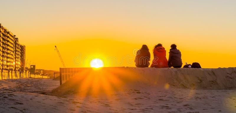 一起坐沙子小山,观看和享受日落在海滩,年轻人的三个少年本质上 免版税库存图片