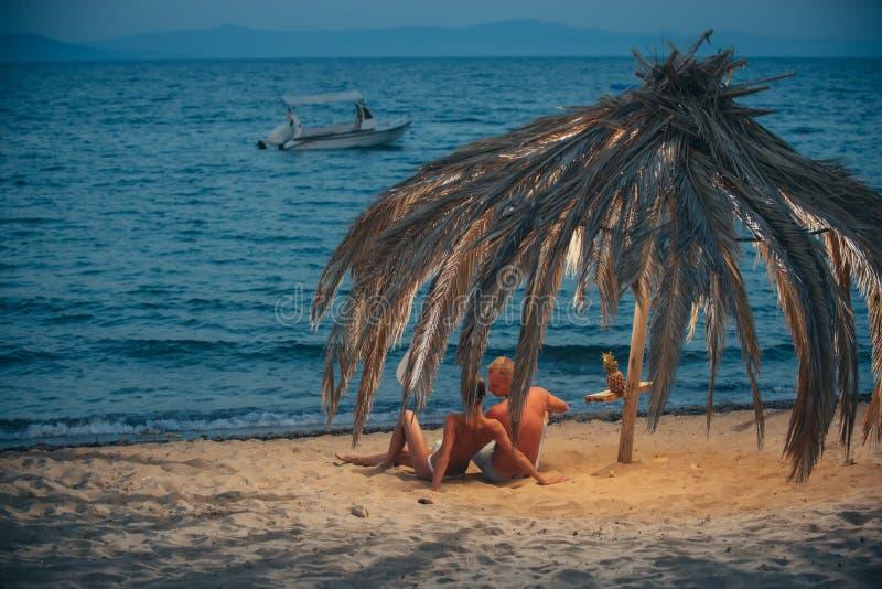 一起坐沙子由海和看对天际的年轻夫妇 库存照片