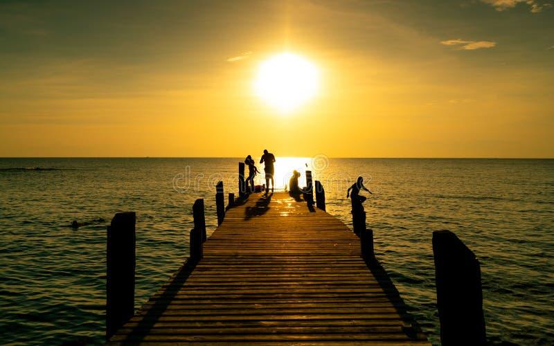 一起幸福家庭戏剧在度假在木桥的暑假在日落 使用在海滩的父母和孩子在度假 库存照片
