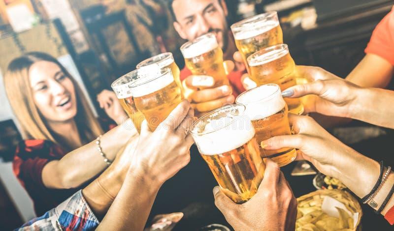 一起喝啤酒的朋友在啤酒厂酒吧餐馆周末-与获得的年轻人的友谊概念乐趣 图库摄影