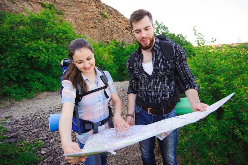 一起搜寻在地图、旅行的旅行,自由和活跃生活方式概念的朋友旅客正确的方向 免版税图库摄影