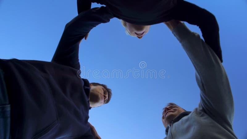 一起拥抱小组的朋友,团队工作导致胜利,底视图 免版税库存照片