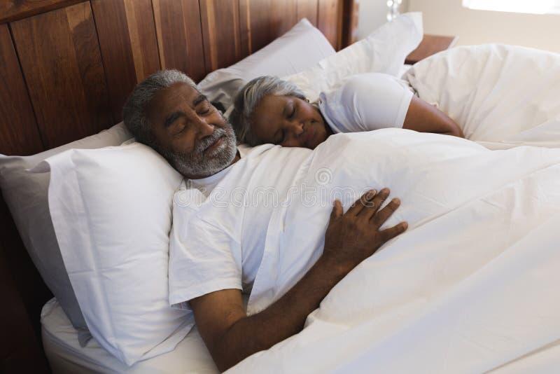 一起睡觉在卧室的资深夫妇 库存照片