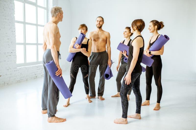 一起站立在瑜伽训练以后的人户内 免版税库存图片