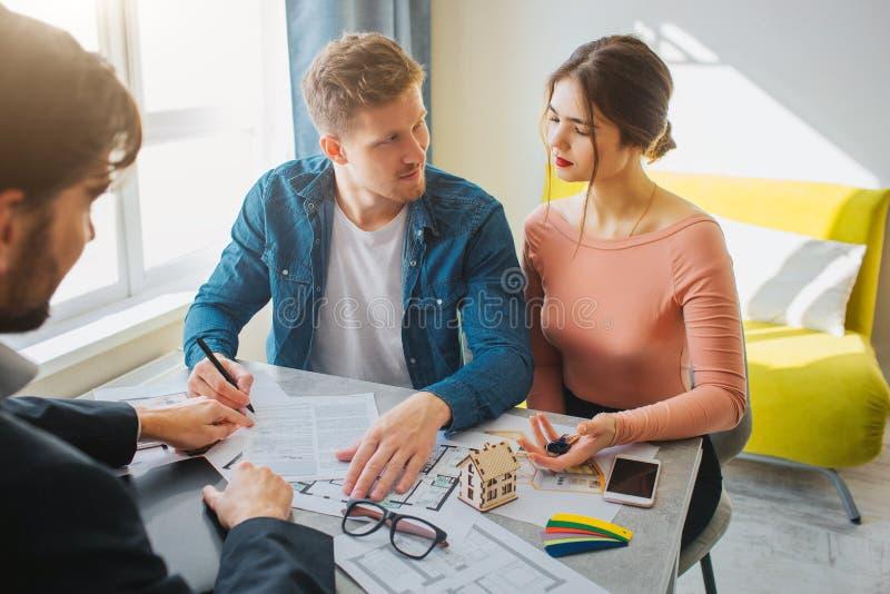 一起结合购买或租公寓 严肃的年轻人和妇女看彼此 人在文件上把署名放 库存照片