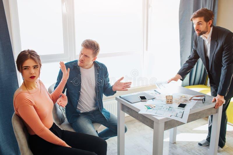 一起结合购买或租公寓 他们互相争论 在他们前面的地产商立场和设法镇定 库存照片