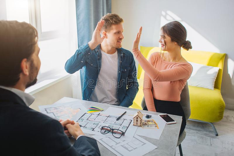 一起结合购买或租公寓 他们互相给高五 地产商坐并且看他们 明亮的阳光 免版税库存图片