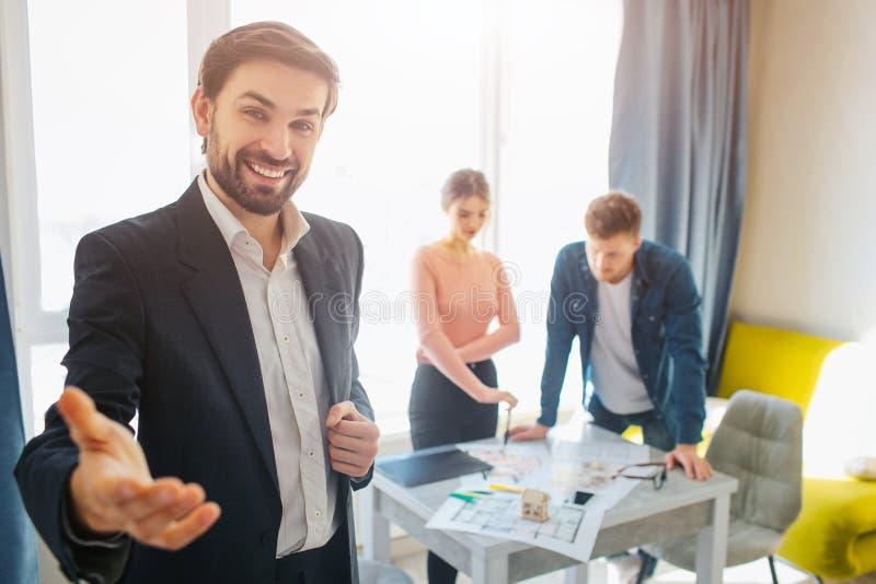 一起结合购买或租公寓 对照相机和微笑的快乐的有胡子的地产商伸手可及的距离手 年轻夫妇立场 免版税库存照片