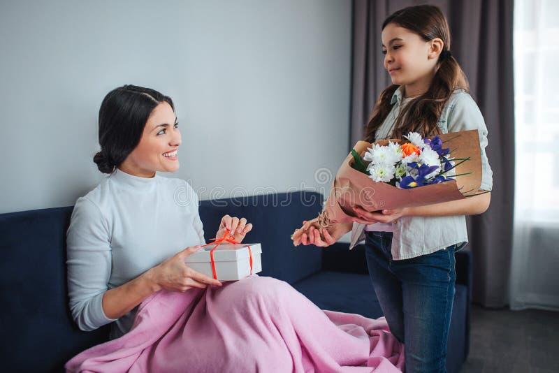 一起美丽的深色的白种人母亲和女儿在屋子里 年轻女人举行白色礼物盒和微笑对女孩 免版税库存图片