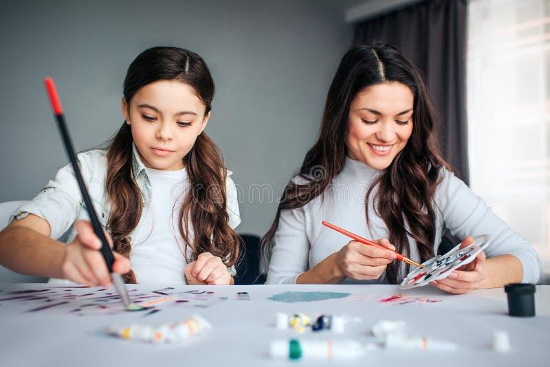 一起美丽的深色的白种人母亲和女儿油漆在屋子里 下来正面年轻女人神色和投入刷子 免版税库存图片