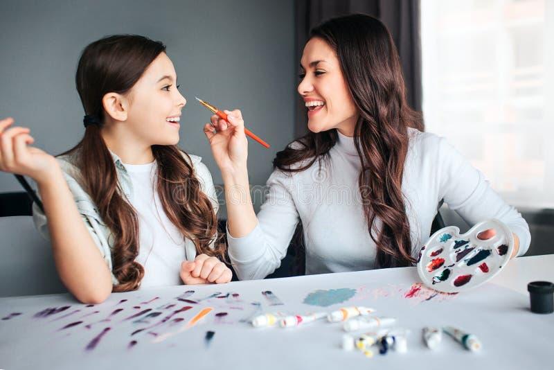 一起美丽的深色的白种人母亲和女儿油漆在屋子里 嬉戏的年轻女人接触女孩的鼻子与 免版税库存图片