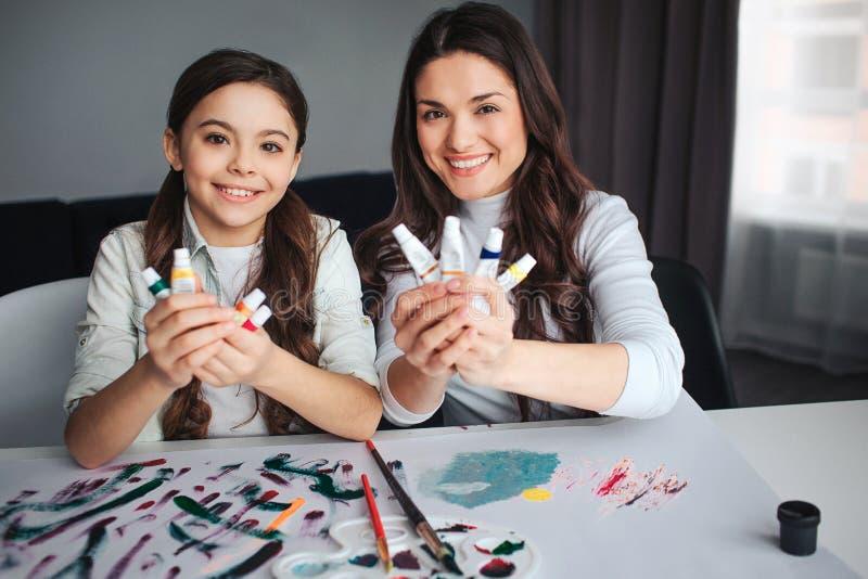 一起美丽的深色的白种人母亲和女儿油漆在屋子里 在照相机和微笑的快乐的愉快的人神色 库存照片