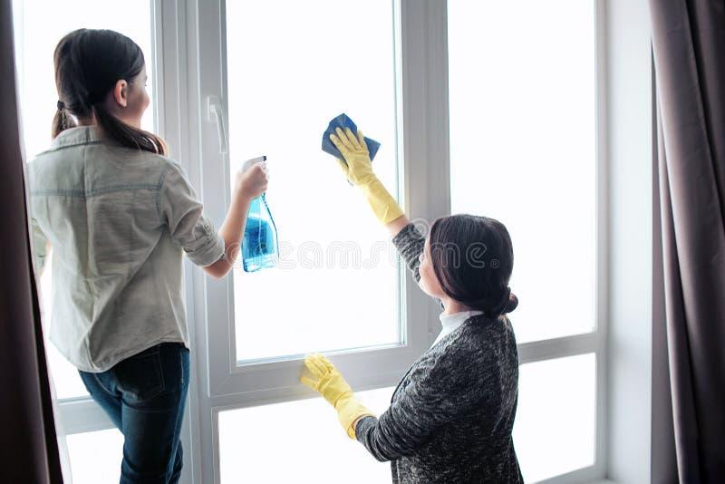 一起美丽的深色的白种人母亲和女儿清洁窗口在屋子里 女孩用途浪花 少妇洗涤物 库存照片