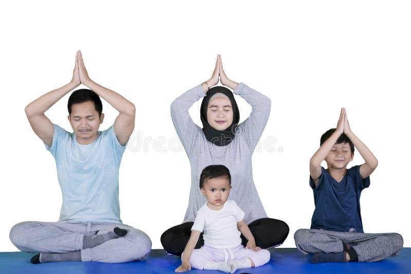 一起行使瑜伽的回教家庭在演播室 库存图片
