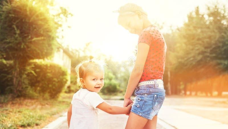 一起走在夏天城市公园的两个妹 家庭价值观概念照片 免版税库存图片