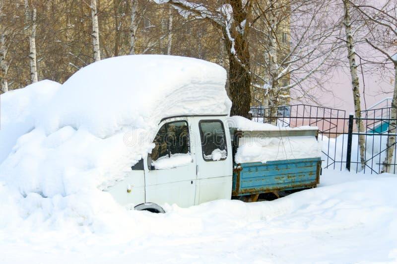 一辆小卡车用雪厚实的层数盖了在围场 图库摄影
