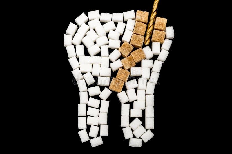 一颗龋受影响的牙的治疗反对黑背景的由糖制成 免版税库存照片