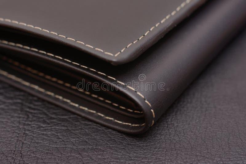 一部分的钱包关闭以黑暗的皮革纹理为背景 免版税库存照片