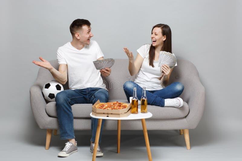 乐趣夫妇妇女人足球迷在美元钞票使金钱振作,现金金钱的支持喜爱的队举行爱好者 免版税库存图片