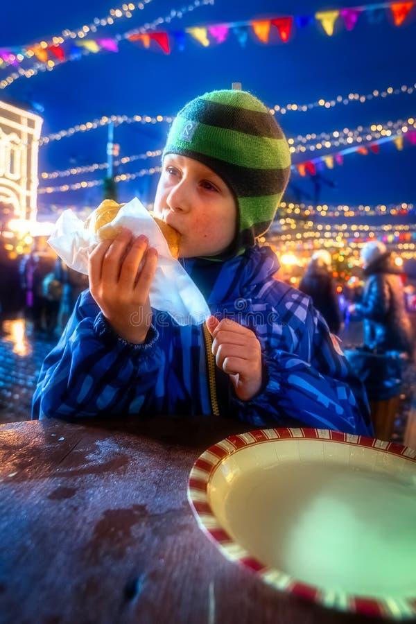 九岁男孩吃着在街道上的温暖的薄酥饼 库存照片