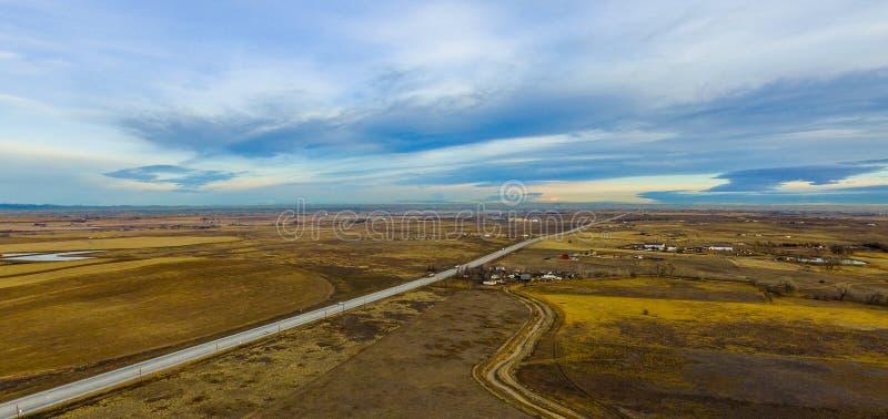 乡下公路通过农厂和大农场土地 免版税库存图片