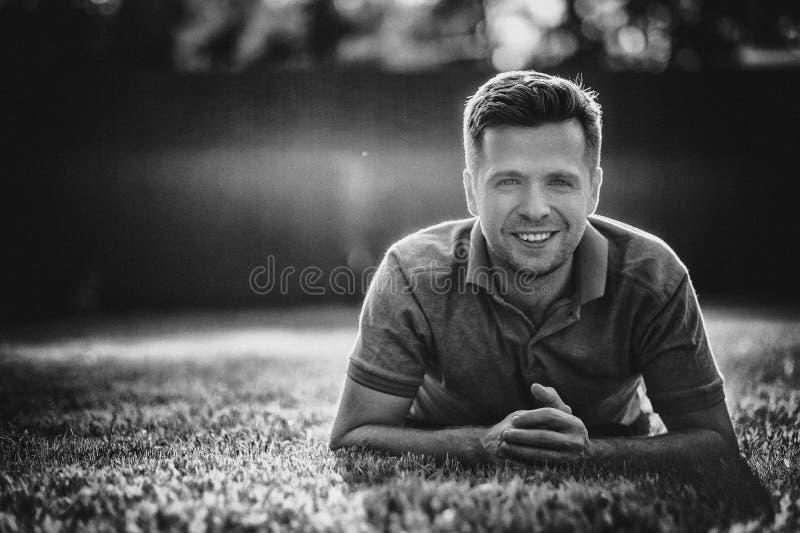 乡下的年轻人看照相机微笑的领域的o 单色照片 库存图片
