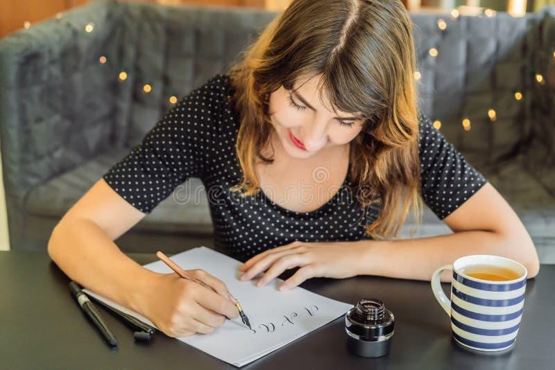 书法家年轻女人在白皮书写词组 关于题写装饰装饰的信件的爱的圣经词组 免版税图库摄影